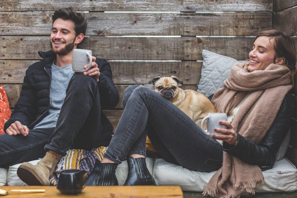 Coppia felice con il cane che beve una tisana